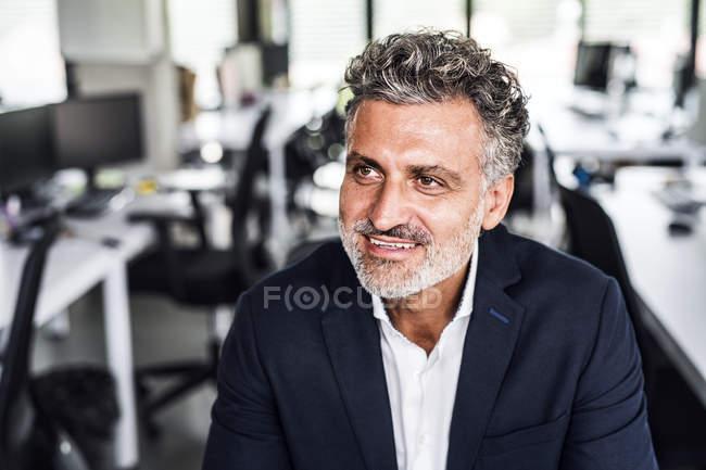 Ritratto di uomo d'affari maturo sorridente che distoglie lo sguardo in ufficio — Foto stock