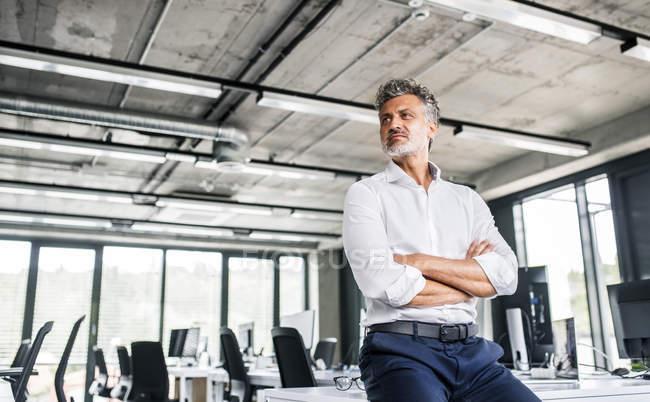 Зрілі бізнесмен сидить на столі в офісі і дивиться боком — стокове фото