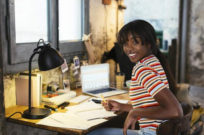 Портрет сміху молода жінка, сидячи на столі в мансарді — стокове фото