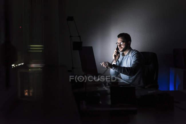 Homme d'affaires au téléphone au bureau la nuit — Photo de stock