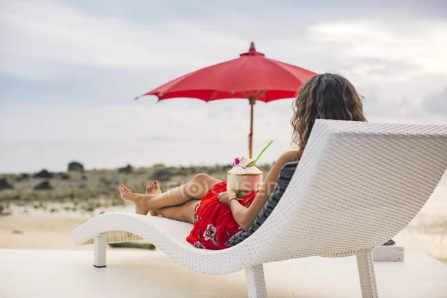 Tailandia, vista trasera de la mujer sentada en la tumbona con coco fresco mirando a la playa - foto de stock