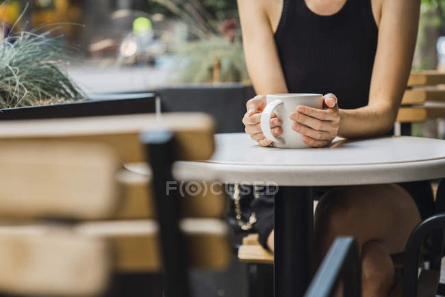 Close-up of woman sitting in coffee shop and drinking tea — Photo de stock