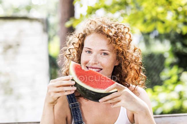 Retrato de mulher jovem ruiva segurando pedaço de melancia na frente do rosto — Fotografia de Stock