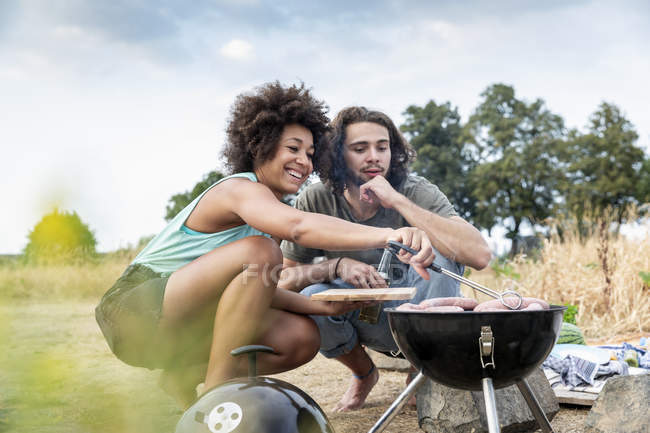 Happy couple having barbecue in nature — стокове фото