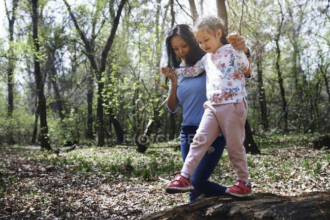 Мать и дочь в парке, девушка балансирует на стволе дерева — стоковое фото