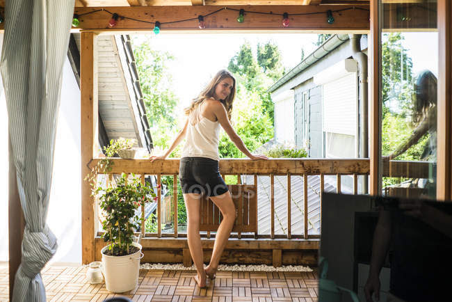 Portrait de femme souriante debout sur le balcon de la maison en bois — Photo de stock