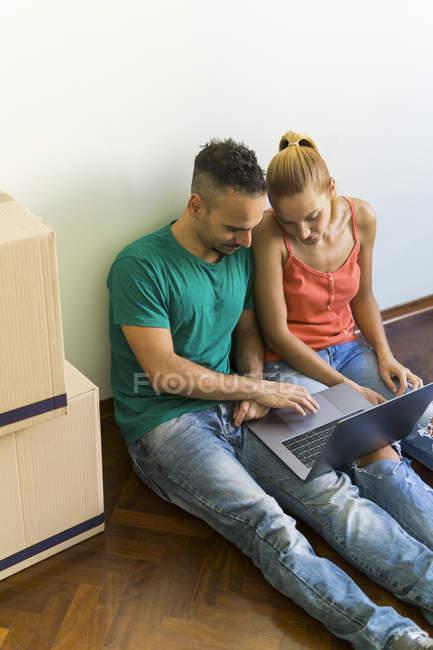 Paar sitzt nebeneinander auf dem Boden des neuen Hauses und schaut gemeinsam auf Laptop — Stockfoto