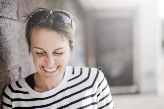 Portrait of laughing woman leaning on wall on street — Stock Photo