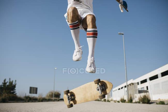 Homme sportif sautant au-dessus du sol avec le tour d'exécution de planche à roulettes — Photo de stock