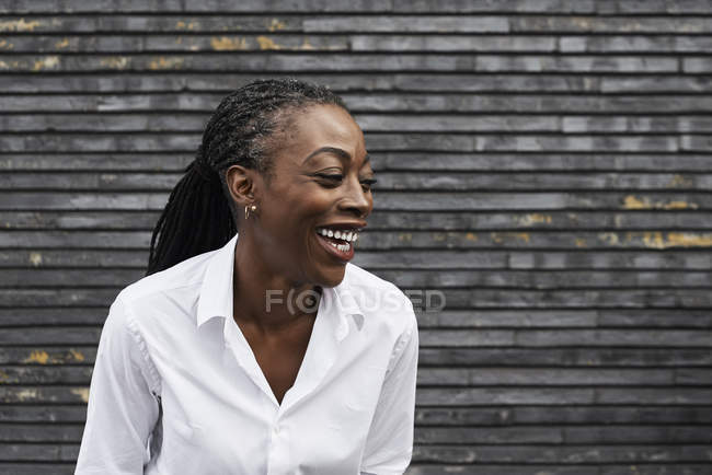 Portrait of laughing businesswoman wearing white shirt — Stock Photo