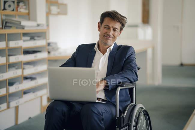 Homme d'affaires en fauteuil roulant, en utilisant un ordinateur portable dans le bureau — Photo de stock