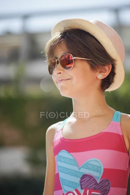 Ritratto di bambina con occhiali da sole e cappello da sole, guardando lateralmente — Foto stock
