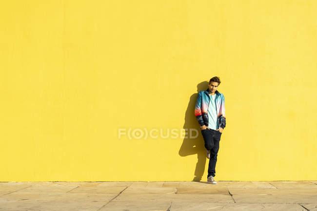 Homme appuyé contre un mur jaune avec les mains dans les poches — Photo de stock