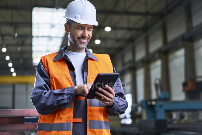 Smiling man using tablet in factory — Stock Photo