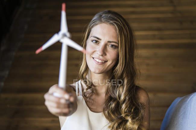 Портрет улыбающейся женщины, держащей модель ветряной турбины — стоковое фото