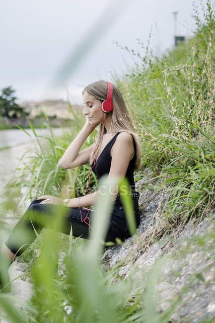 Smiling teenage girl wearing headphones listening to music at riverside — Stock Photo