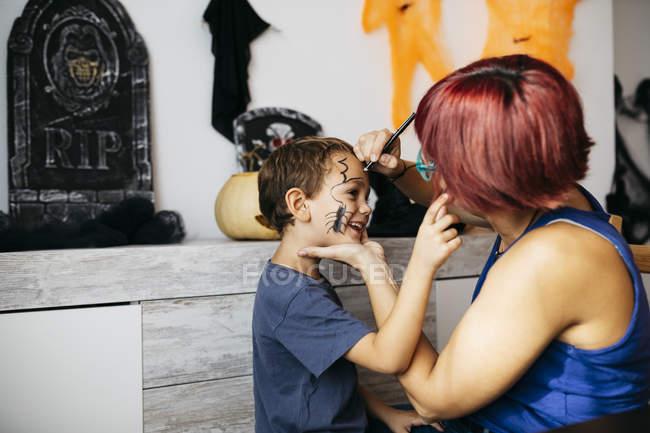 Mère peignant une araignée sur le visage de son fils pour l'Halloween — Photo de stock