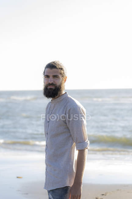 Portrait of young bearded man standing at sea — Stock Photo