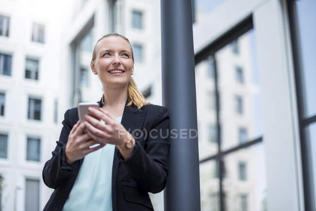 Портрет улыбающейся деловой женщины с телефоном в ожидании — стоковое фото