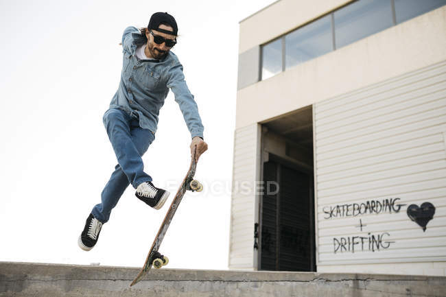 Trendy man in denim and cap skateboarding, doing jump with skateboard from concrete ramp — Foto stock