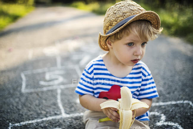 Portrait of toddler boy with banana sitting on the street and watching something — Stock Photo