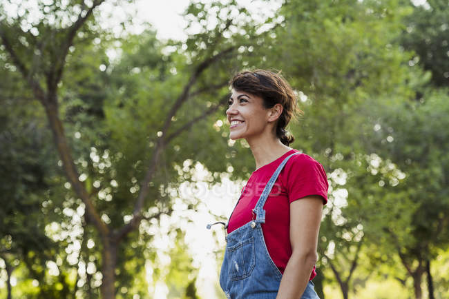 Smiling woman in denim jumpsuit relaxing in nature — Stock Photo