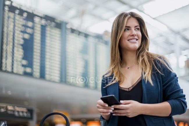 Улыбающаяся молодая женщина с мобильным телефоном на борту вылета оглядывается вокруг — стоковое фото