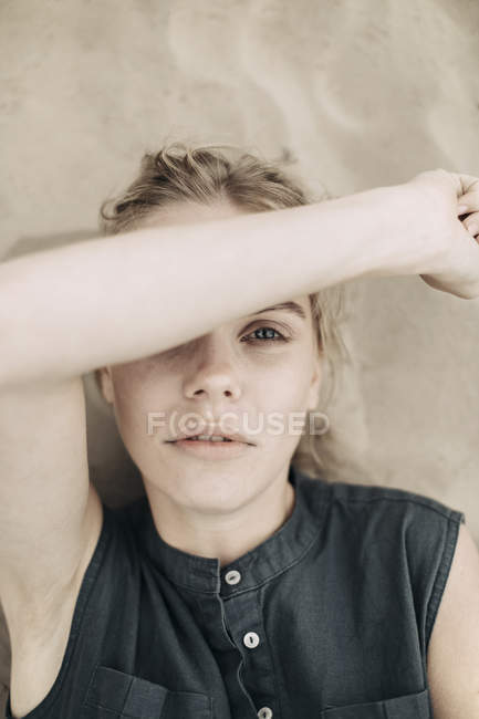 Retrato da mulher nova que encontra-se no olho da coberta de areia com seu braço — Fotografia de Stock