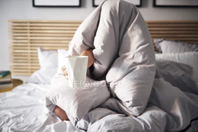 Mulher escondida o café de exigência do cobertor — Fotografia de Stock