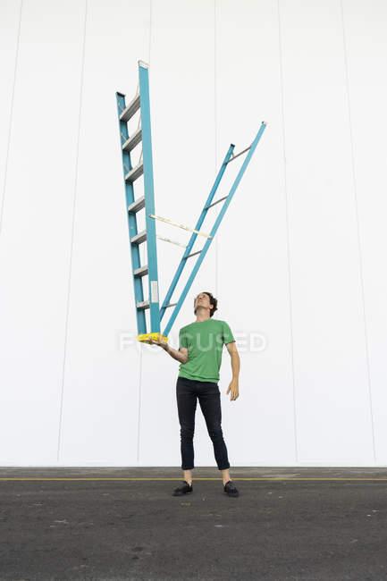 Acrobat balanceo escalera al revés en su mano - foto de stock