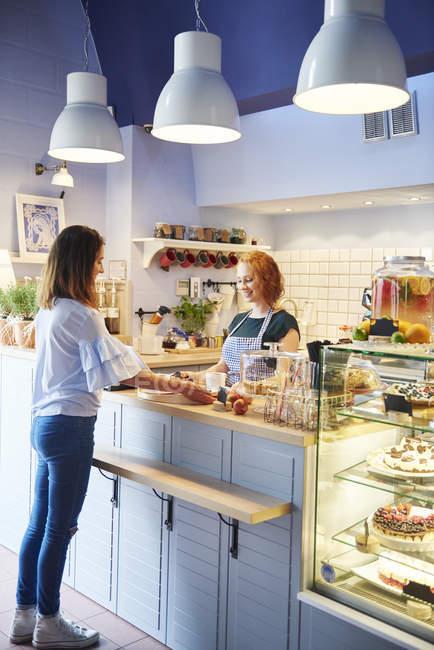 Cliente y camarera en el mostrador en un café - foto de stock