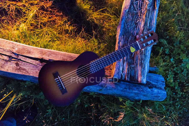 Guitar on wood beam by a campfire — Stock Photo