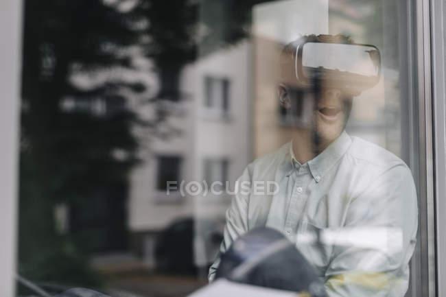 Giovane seduto alla finestra e utilizzando occhiali VR — Foto stock
