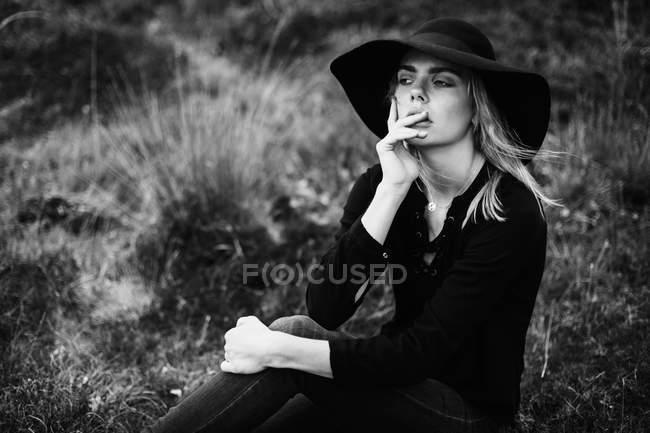 Портрет молодої жінки в чорному капелюсі і позує, зберігаючи пальці на губах — стокове фото