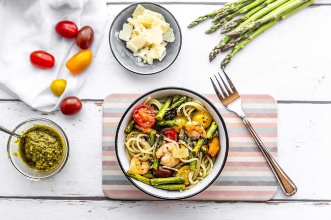 Спагетти с креветками, зеленой спаржей, помидорами, песто и пармезаном — стоковое фото
