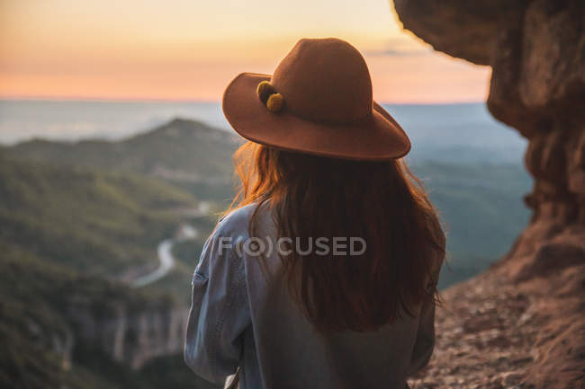 Rear view of woman on hiking trip looking at view at sunset — Stock Photo