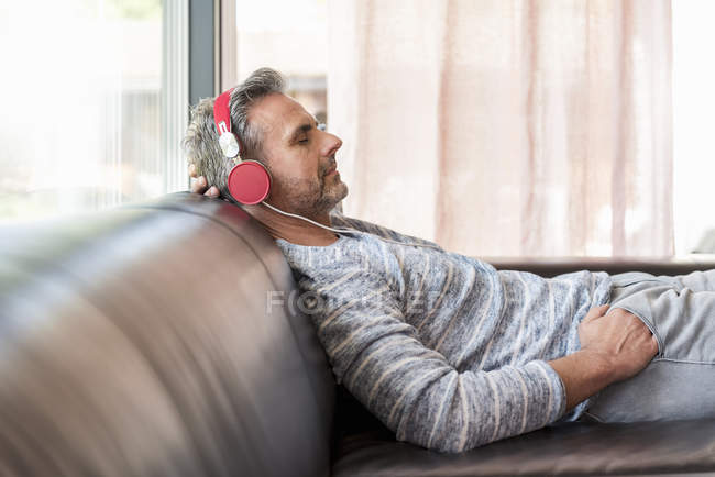Relaxed mature man lying on couch at home wearing headphones — Stock Photo