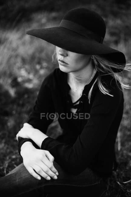 Ritratto di giovane donna con cappello nero e posa sulla macchina fotografica — Foto stock