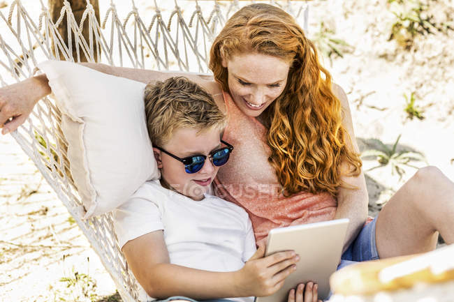 Happy mother and son lying in hammock looking at tablet — Stock Photo