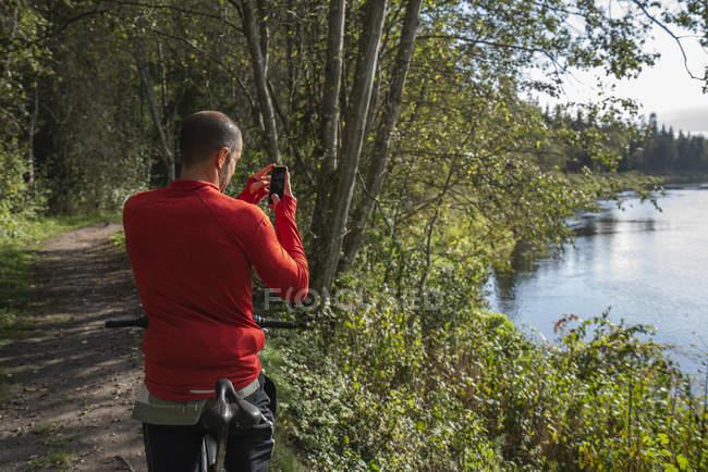 Montanha motociclista de pé no lago tirar foto com smartphone — Fotografia de Stock