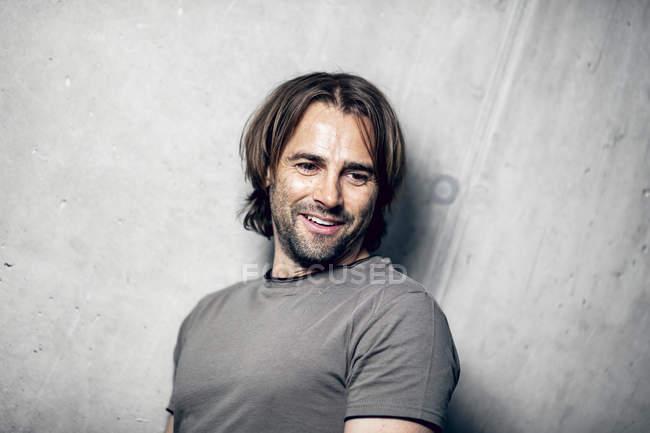 Verticale d'athlète de sourire au mur en béton — Photo de stock