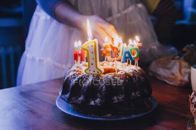 Frau zündet Geburtstagskuchenkerzen an, Teilansicht — Stockfoto