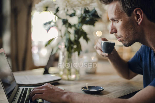 Mid adult man sitting in coffee shop, drinking coffee, using laptop — Stock Photo