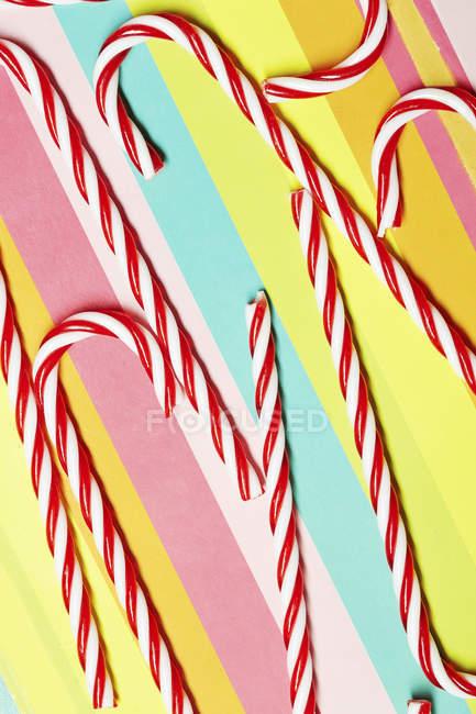 Cannes à bonbons sur papier multicolore — Photo de stock