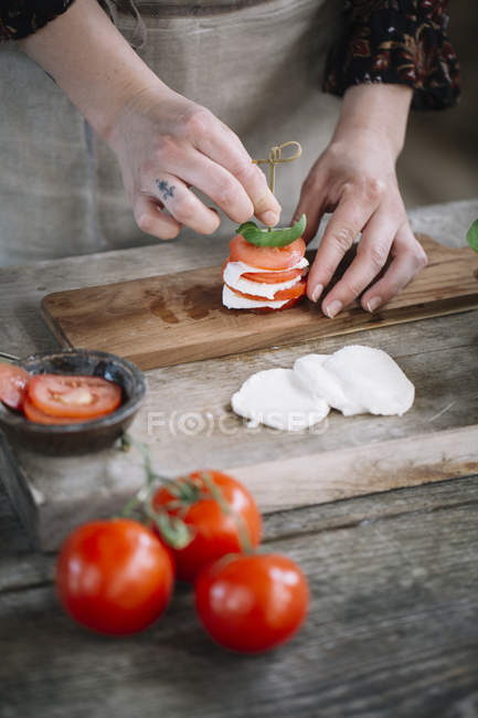 Woman's hands preparing Caprese Salad — Stock Photo