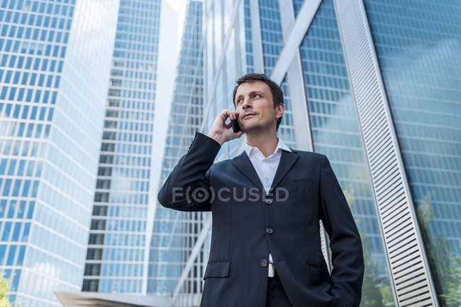 Businessman on cell phone in the city — Stock Photo