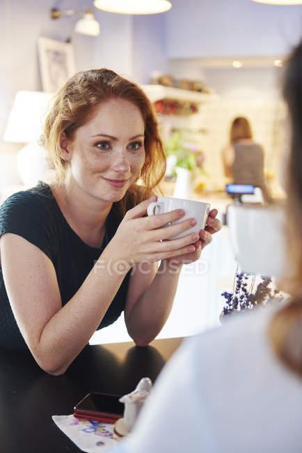 Lächelnde junge Frau trinkt Kaffee mit Freundin im Café — Stockfoto