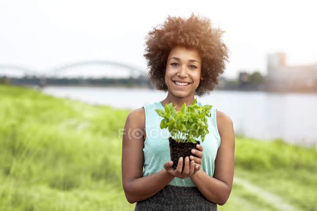 Retrato de mulher sorridente segurando planta ao ar livre — Fotografia de Stock