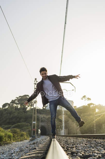 Молодой человек стоит на железнодорожном пути — стоковое фото