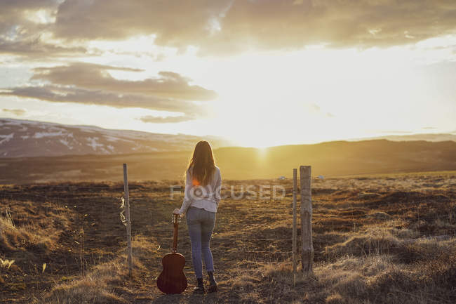 Iceland,  young woman with guitar at sunset — Stock Photo